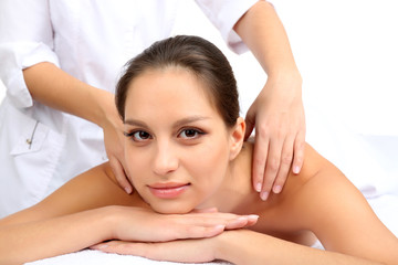 Masseur doing massage on woman body isolated on white.