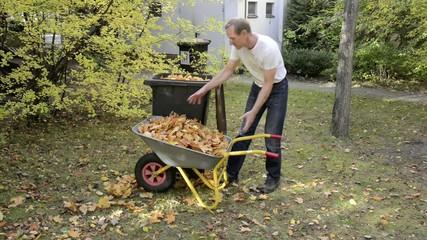 Mann füllt Laub in Mülltonne