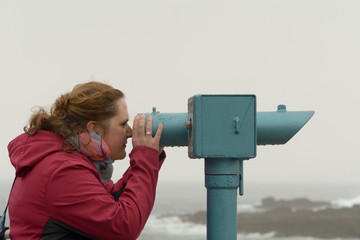 woman looking through blue telescope