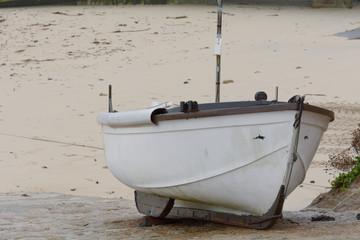 Small white fishing boat on ramp