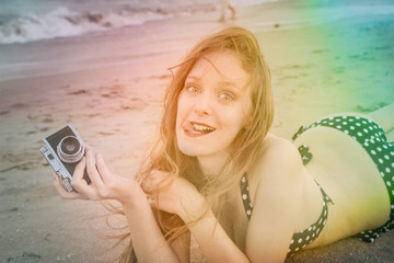 Happy girl at the beach holding a camera and making jokes