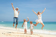 Happy family jumping on the beach on the day time - 73716939