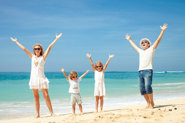 Happy family jumping on the beach on the day time