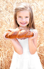 Smiling little girl on field of wheat