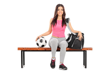 Female football player sitting on a bench