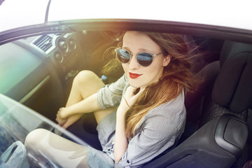 Wonderful young woman sitting in a car