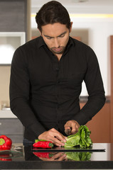 handsome young man cooking in modern kitchen