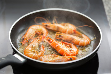 Fresh shrimps being fried in olive oil