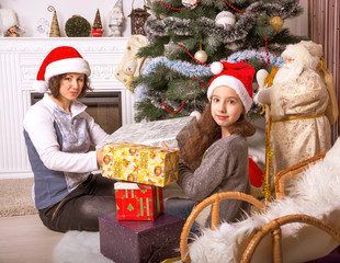 Mom and daughter with gifts under the Christmas tree.