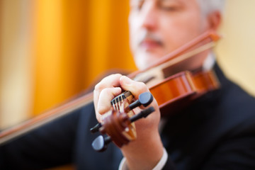 Man playing his violin in a concert hall