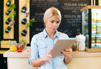 Owner of small restaurant holding a digital tablet