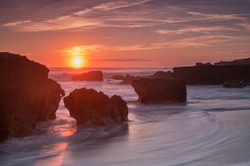 Beautiful sea sunset on the waves. Sandy beach.