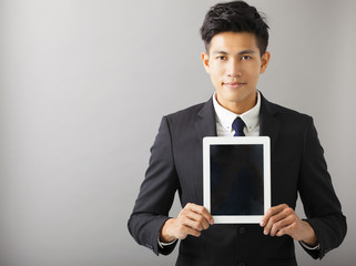 young smiling business man showing tablet pc