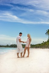 Man and woman at the snow white sand beach
