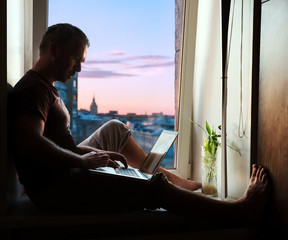 Silhouette of man on window sill with laptop