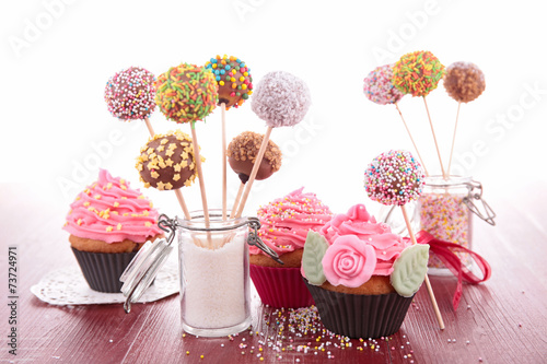 colorful cake pops and cupcake - 73724971