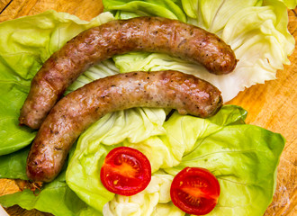 Sausage on wooden cutting board with salad top view