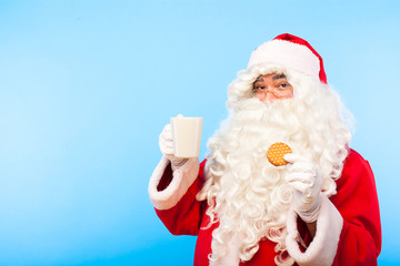 santa claus with a cup of coffee or tea and a biscuit on blue ba
