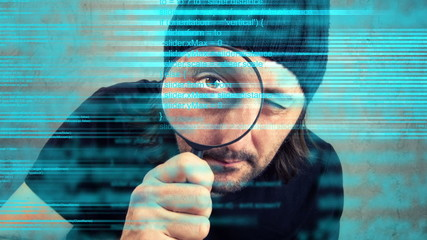 Man looking through magnifying glass and inspecting code