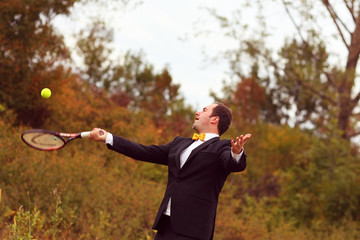 Happy groom playing tennis in his wedding day