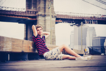 Young adult relaxing next to Brooklyn Bridge