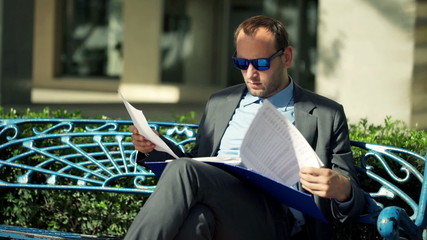 Young businessman reading documents on the bench in the city