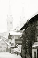 Verschneites Dorf mit Kirche in Schwarz Weiss