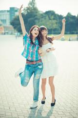 beautiful hipster young women sisters friends dancing