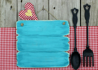 Blank blue wood menu sign with cast iron spoon and fork