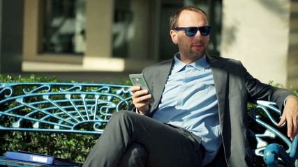 Young, handsome businessman sitting with smartphone on the bench