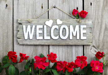 Wooden welcome sign with flower border of red roses