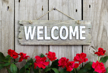 Welcome sign with row of red flowers with wooden background