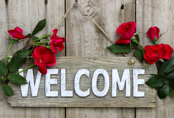 Welcome sign with red flower border on wooden background
