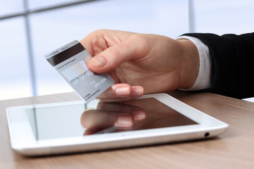 Young business woman  holding  a credit card . On-line shopping