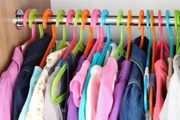 Closet with baby dresses on hangers