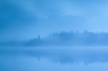 mountains and forest by Barmsee lake in fog