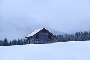 old wooden hut in snowy meadow in Alps