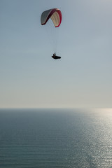 Lone paraglider flying high over the ocean