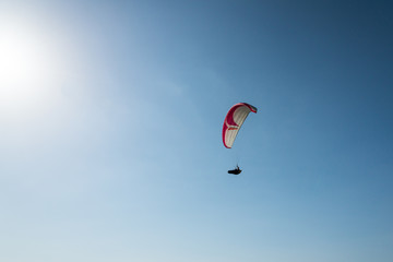 Lone paraglider flying high towards the sun