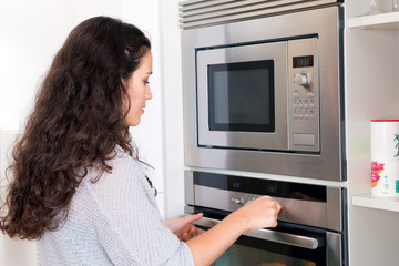 Young woman programming the oven
