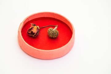 Dried small rose and a heart shaped bean