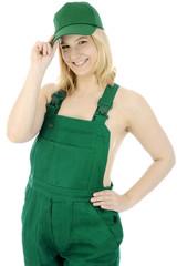 Gärtnerin in grüner Latzhose grüßt freundlich