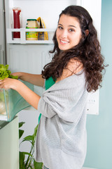 Young woman taking out a lettuce from refrigerator