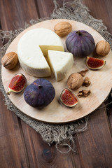 Fig fruits, cheese and walnuts over rustic wooden background