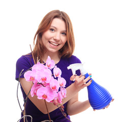Pretty girl watering orchid flower with spray