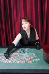 sexy girl wearing in a black dress and gloves plays in casino
