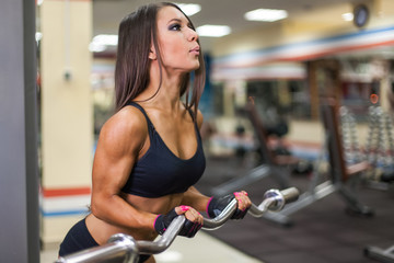 bodybuilder girl with barbell in gym