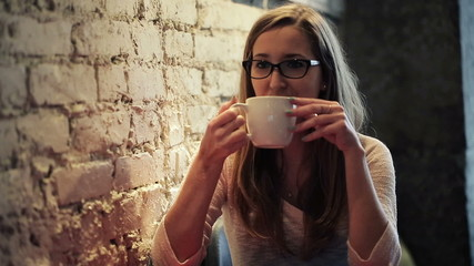 Portrait of smiling cute woman drinking tea in cafe