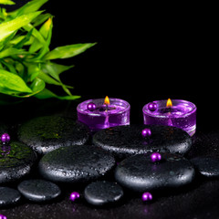 spa concept of zen basalt stones with drops, lilac candles, bead