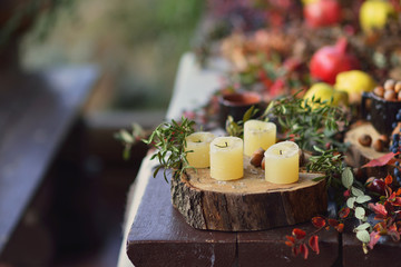 on a wooden table foliage stump with white candles and fruit